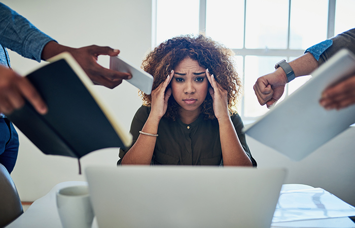 A stressed, African American woman sits at a laptop. employers need to reduce the risk of employee burnout.